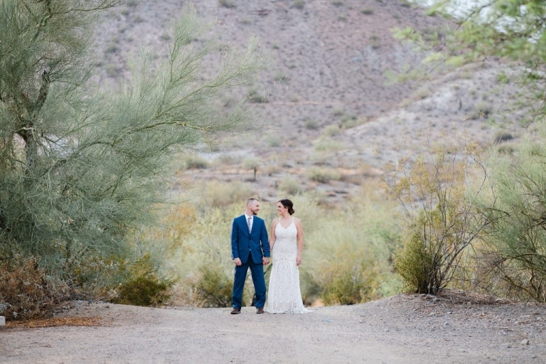 Bride and groom holding hands in desert during intimate phoenix elopement