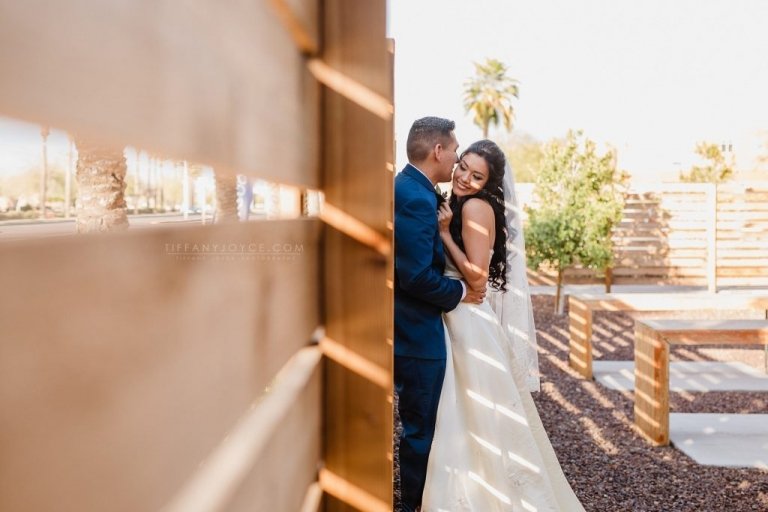 Couple snuggling against wall at downtown phoenix wedding